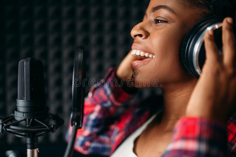 女歌手歌曲在录音演播室 免版税库存照片