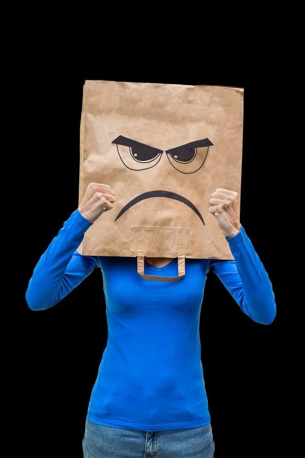 女服与恼怒的面孔的纸袋在黑背景 免版税库存照片