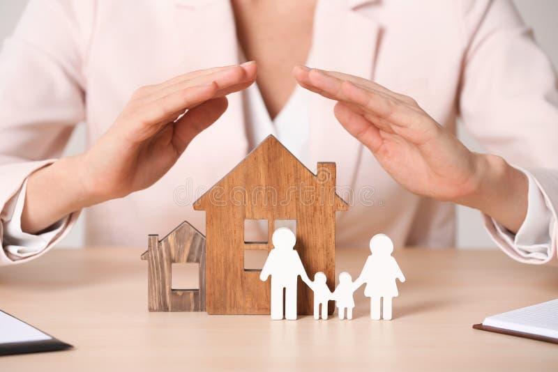 女性代理盖木房子的和家庭在桌上 家庭保险 免版税库存照片