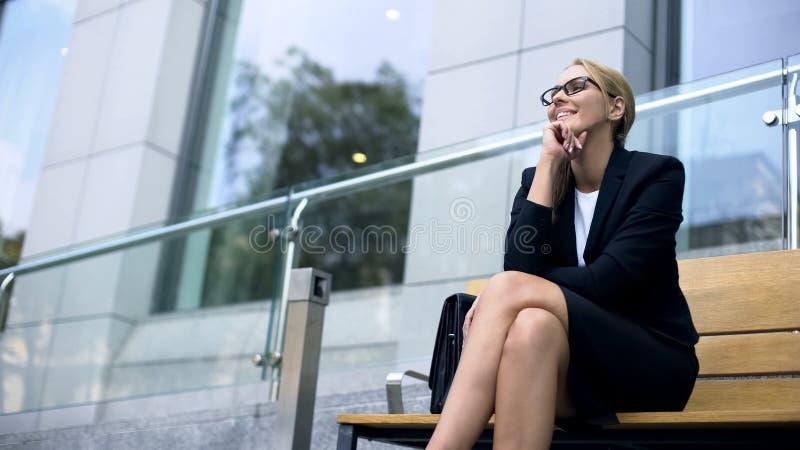 女性企业家坐长凳,微笑,高兴对成功的天 免版税图库摄影