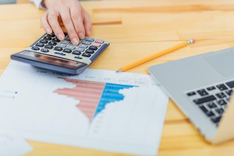 女性会计使用一个计算器总结相当数量收入、费用和每年统计总结的 库存图片