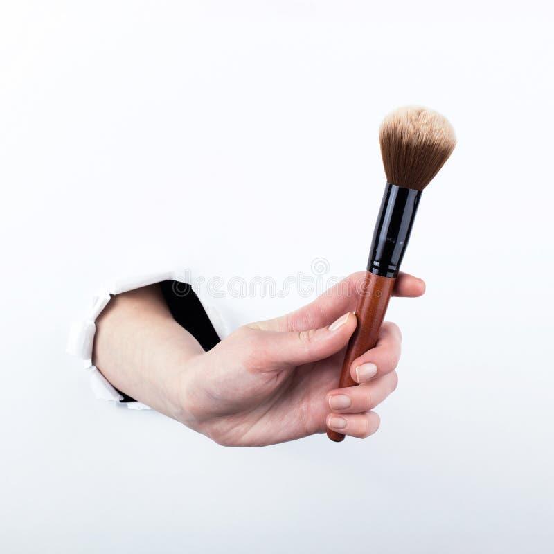 女性实施在纸的一个孔,拿着一把大粉末刷子 在空白背景的孤立 免版税库存图片