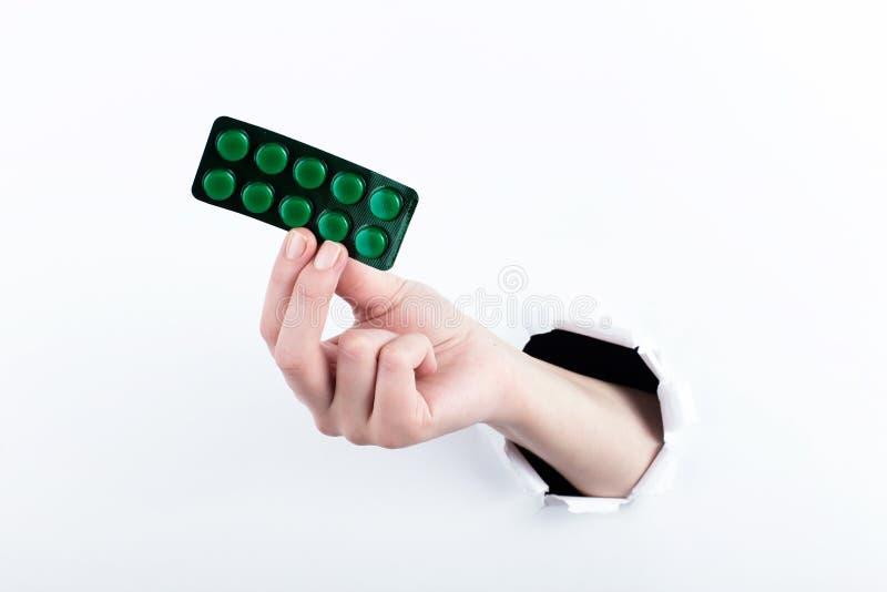 女性实施在paperman的孔,握有药片的水泡 在空白背景的孤立 库存图片