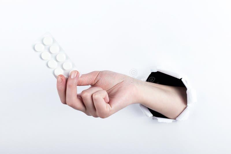 女性实施在paperman的孔,握有药片的水泡 在空白背景的孤立 免版税库存图片