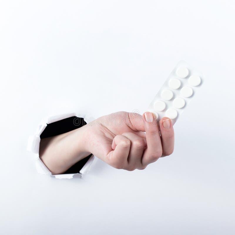 女性实施在paperman的孔,握有药片的水泡 在空白背景的孤立 免版税图库摄影