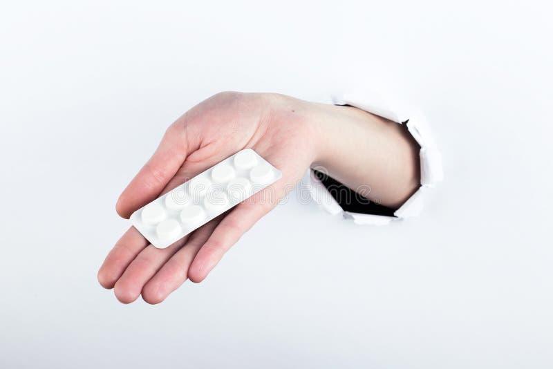 女性实施在paperman的孔,握有药片的水泡 在空白背景的孤立 库存照片