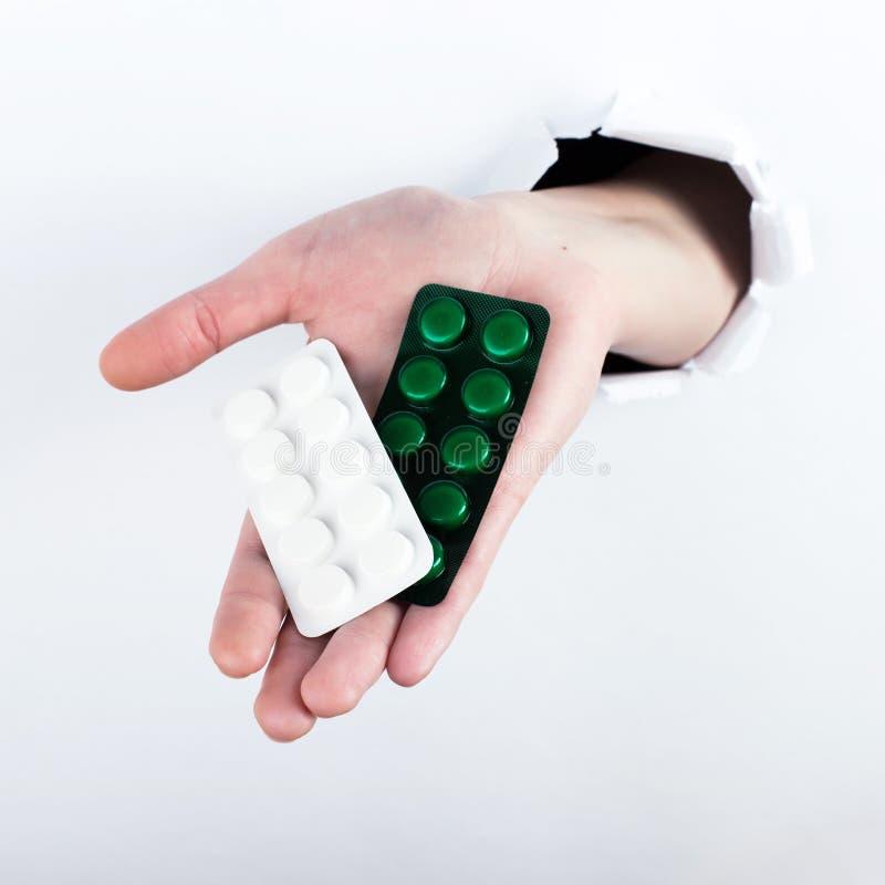 女性实施在paperman的孔,握有药片的水泡 在空白背景的孤立 免版税库存照片
