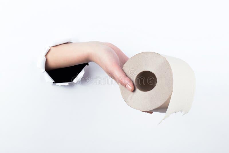 女性实施在paperman的孔,拿着手纸卷  在空白背景的孤立 免版税库存图片