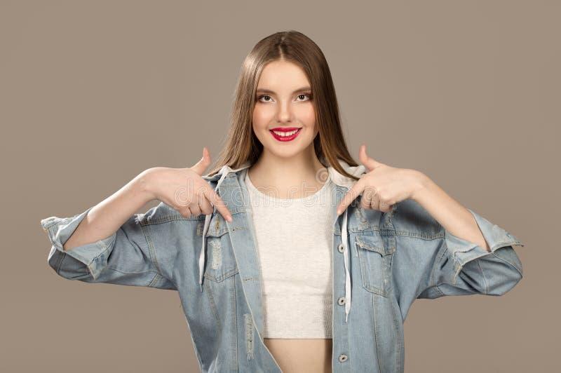 女性少年笑,指向空的空间 Sopycpase 明亮的美好构成和的时尚 库存图片