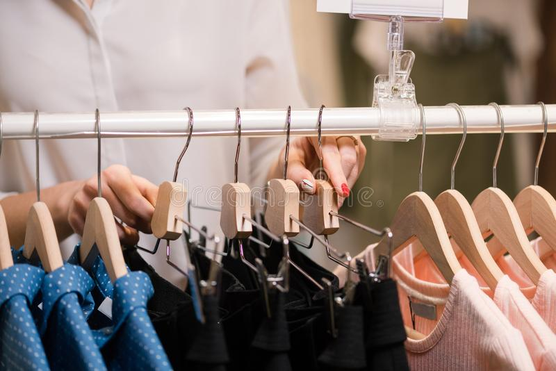 女性手在与挂衣架的立场上把衣裳放 免版税图库摄影