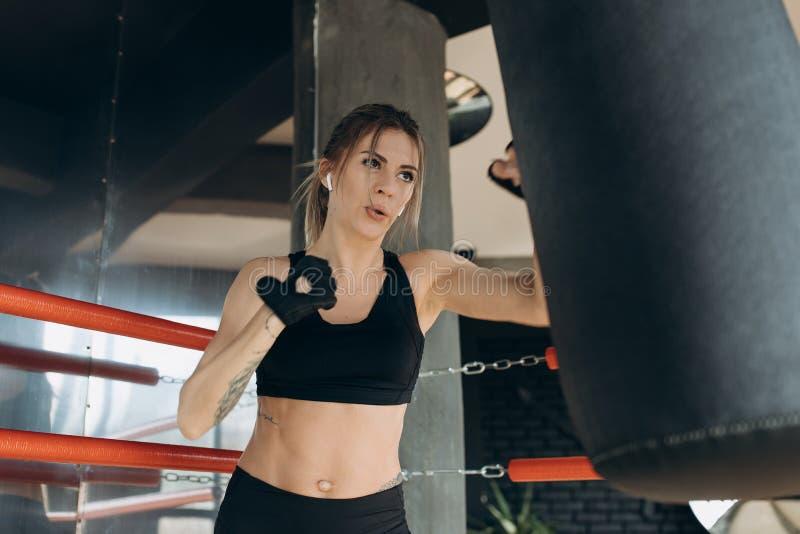 女性猛击与拳击手套的一个把装箱的袋子在健身房 库存图片