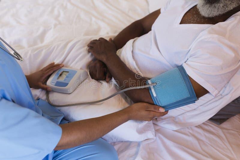 女性老人医生测量的血压在家 库存图片