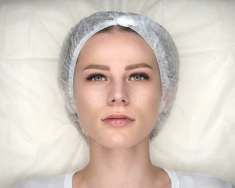 女性面孔与新的错误鞭子和在一次性盖帽 妇女,在睫毛引伸做法在长沙发后说谎 免版税库存图片