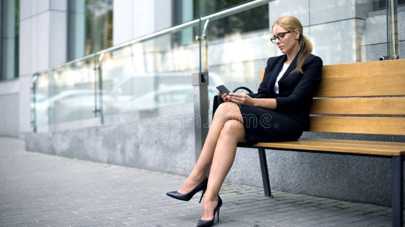 女性雇员坐长凳在工作日以后,使用电话叫出租汽车 免版税库存图片