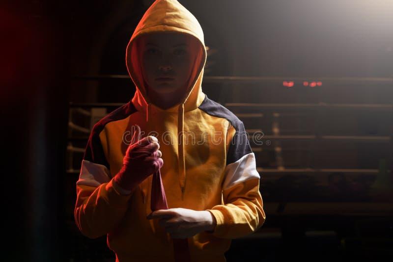 女运动员拳击手在她的在圆环的手附近拉扯红色绷带 免版税库存照片