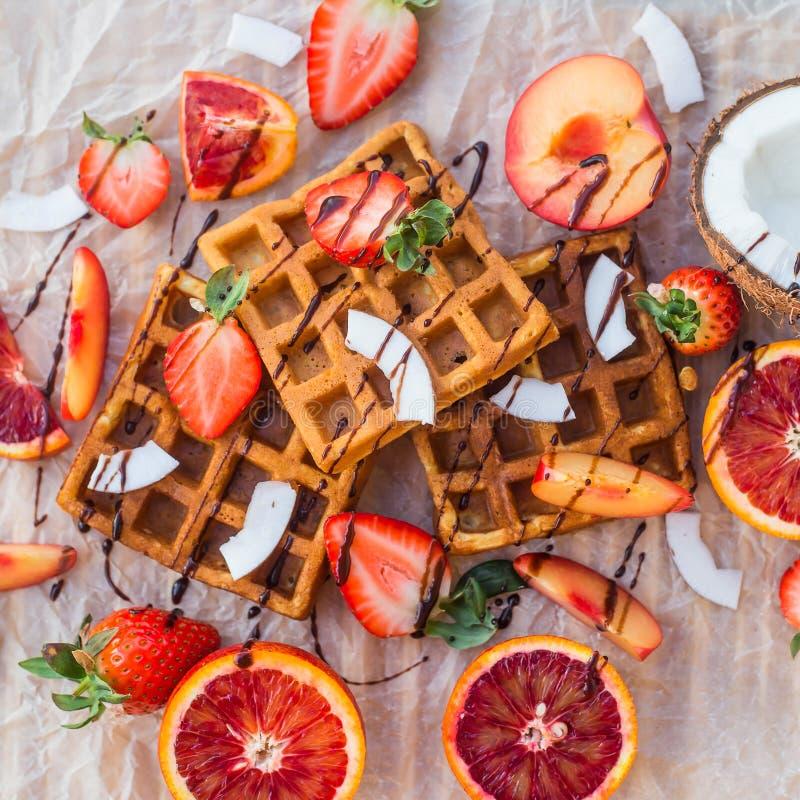 奶蛋烘饼用草莓、椰子、李子和桔子用巧克力 免版税库存图片
