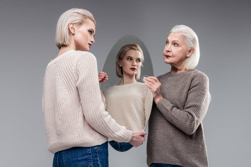 好奇老拿着镜子的边母亲和她美丽的女儿 库存照片
