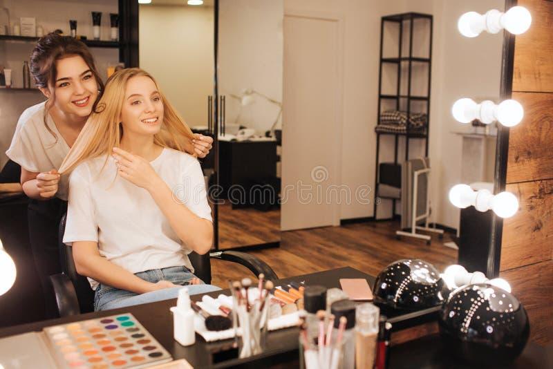 好的快乐的年轻人组成在白肤金发的模型后的艺术家立场和微笑给她在秀丽屋子里 她举行她的头发和神色 免版税库存图片