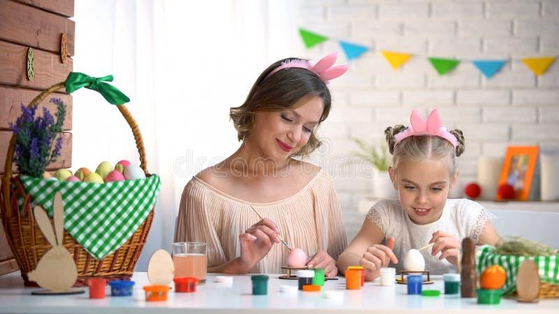 妈妈和女孩上色鸡蛋复活节的头饰带的,开发的强的联系 库存照片