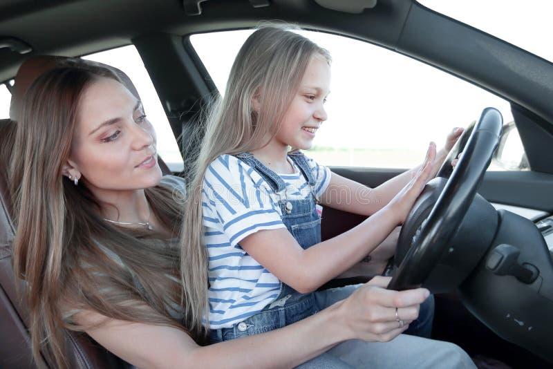 妈妈教她的小女儿驾驶 免版税库存照片