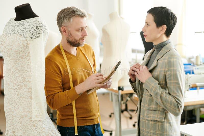 妇女与裁缝协商 免版税库存照片