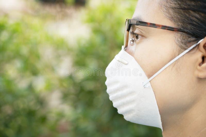 妇女佩带的面膜的关闭为保护在室外的尘土 库存图片