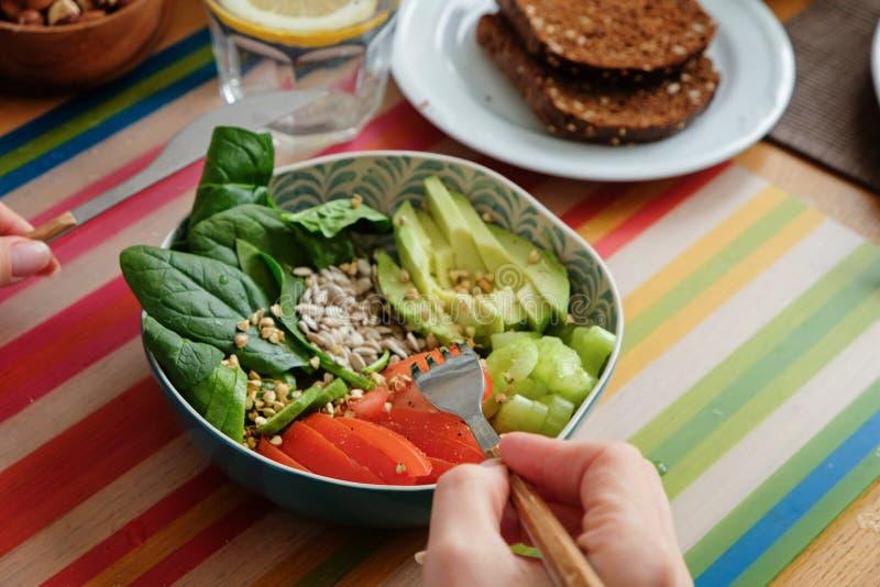 妇女吃着在五颜六色的背景的健康午餐 菩萨碗 健康概念的食物 免版税库存照片
