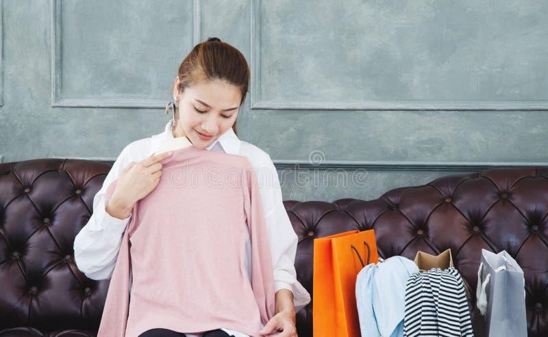 妇女坐沙发她拿着一件桃红色衬衣和微笑着 免版税库存图片