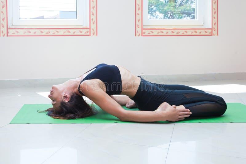 妇女实践瑜伽室内舒展充分的身体射击 免版税图库摄影