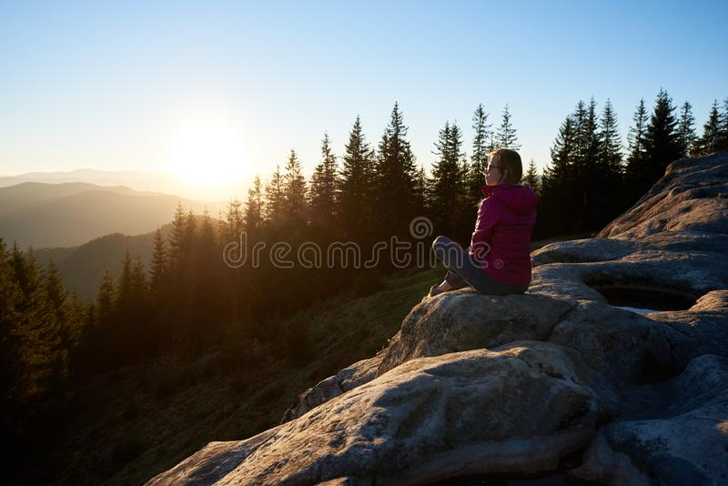 妇女徒步旅行者坐在山的冰砾在日落 免版税图库摄影