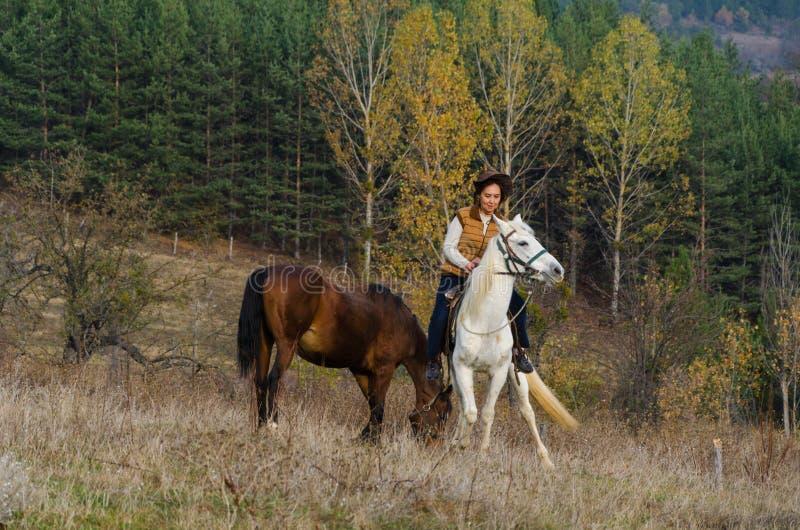 妇女在一个白马乘坐 免版税库存图片