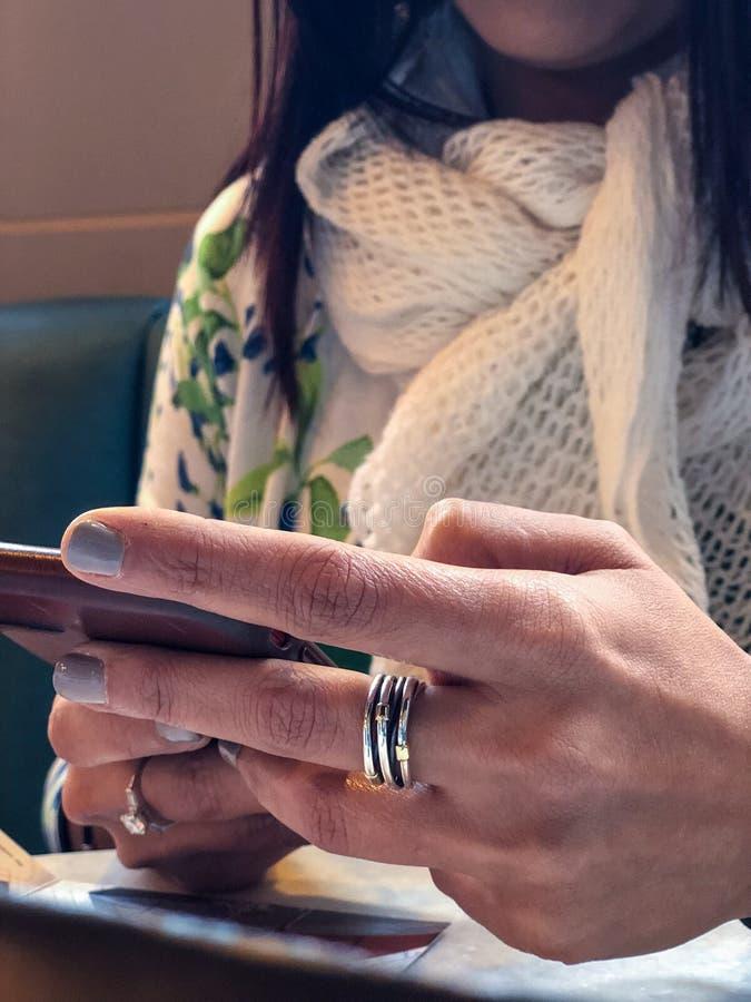 妇女在她的手上拿着手机 库存图片