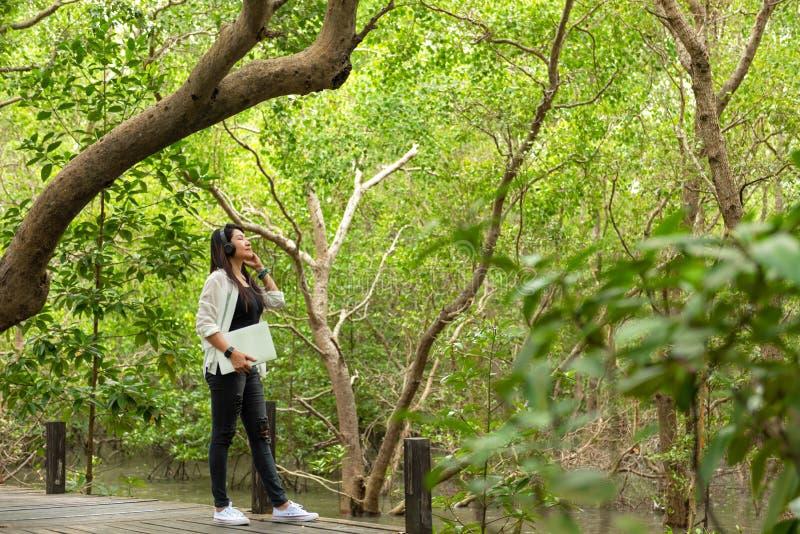 妇女在室外教育自然绿色公园放松并且变冷,当与耳机和膝上型计算机,愉快时的女孩的听的音乐 免版税库存照片