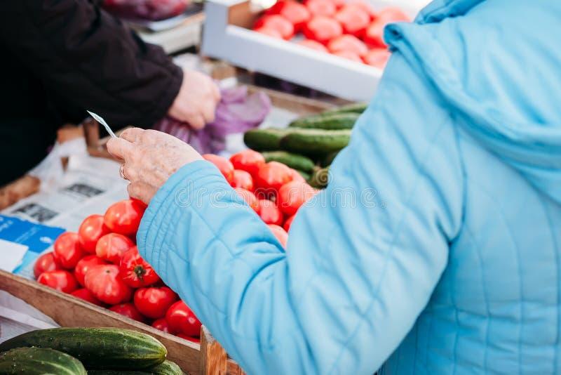 妇女在市场上买产品 支付物品金钱 库存照片