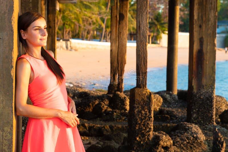妇女在海滩站立在晚上 日落的女孩 享受太阳的最后光芒的可爱的少女 库存图片