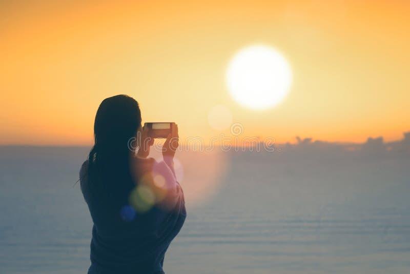 妇女剪影有在毯子包裹的湿头发的在游泳以后 在手机身分的女性采取的图片在海滩 库存照片