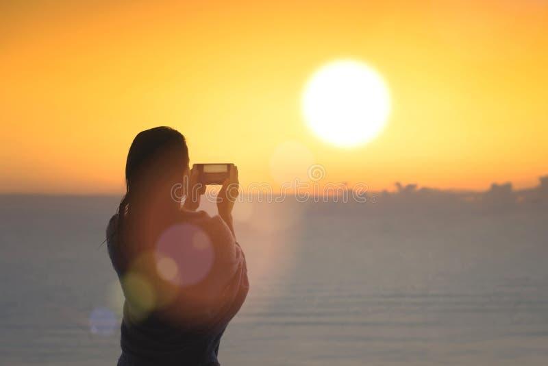 妇女剪影有在毯子包裹的湿头发的在游泳以后 在手机身分的女性采取的图片在海滩 免版税库存照片