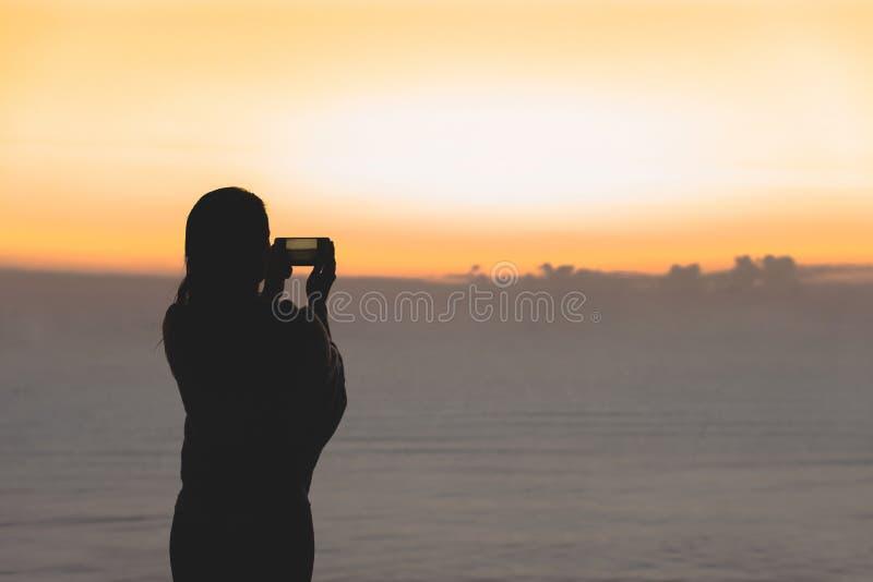妇女剪影有在毯子包裹的湿头发的在游泳以后 在手机身分的女性采取的图片在海滩 库存图片