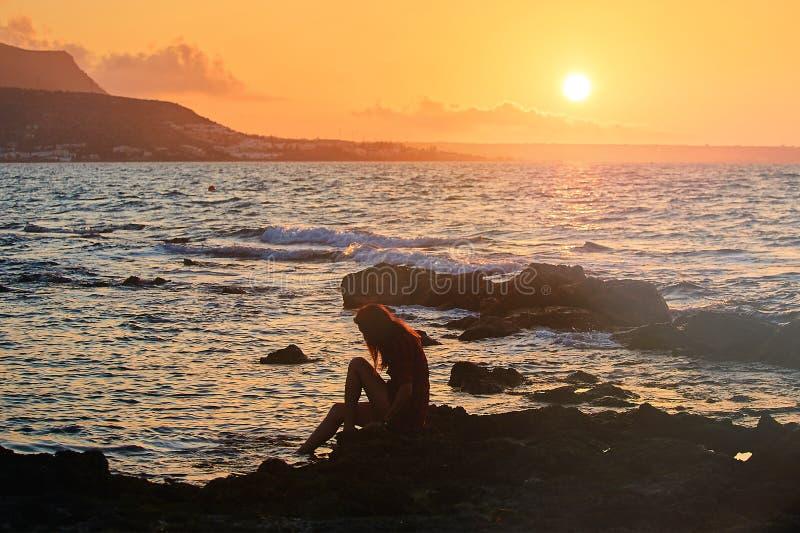 妇女剪影观看的太阳的外形在海滩的在日落和山 免版税库存图片