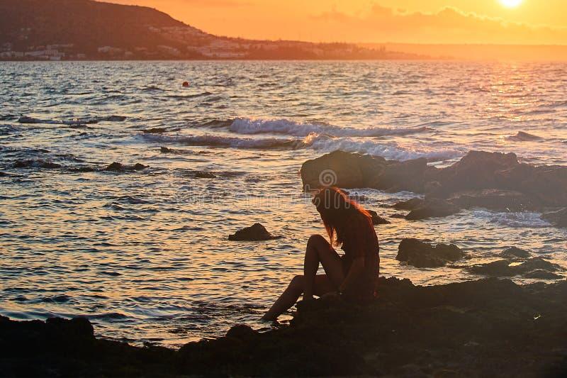 妇女剪影观看的太阳的外形在海滩的在日落和山 库存照片