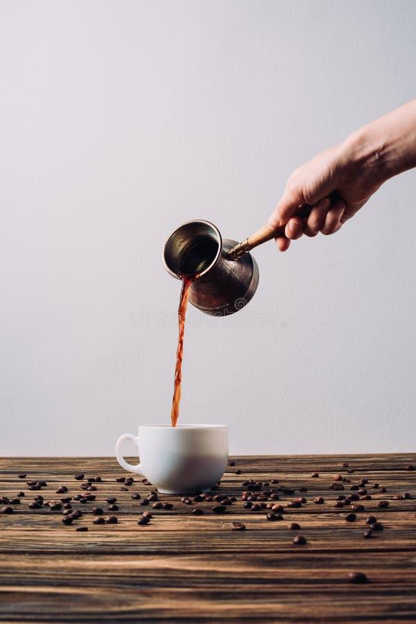 妇女倾吐的咖啡播种的射击到从cezve的杯子里在土气 图库摄影