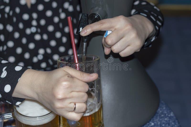 妇女倒从一台桌面冷却的分配器的新鲜的冰镇啤酒入啤酒杯 免版税图库摄影