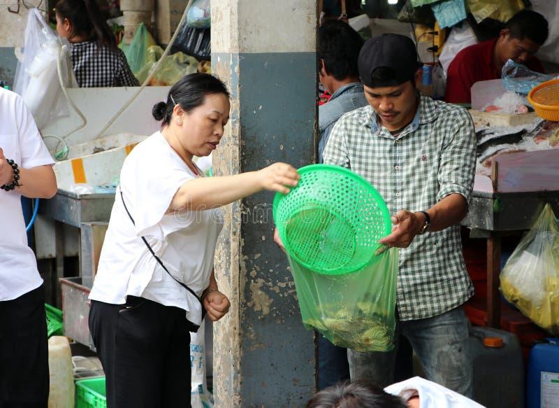 妇女倒从篮子的虾入塑料袋在新鲜市场在中环街市,与不计其数的摊位的一个大市场上 免版税库存图片