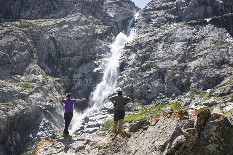 妇女和人徒步旅行者在岩石赤足站立并且享受瀑布视图 库存图片
