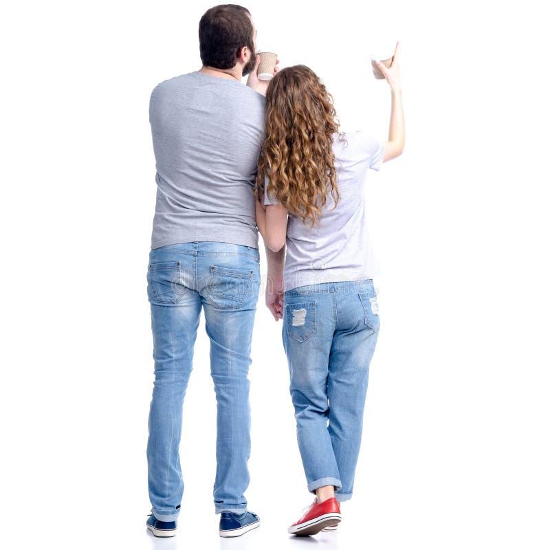 妇女和人站立的牛仔裤的看在手中显示,与纸板咖啡 免版税库存图片