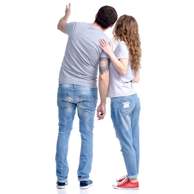 妇女和人站立的牛仔裤的看显示 库存照片
