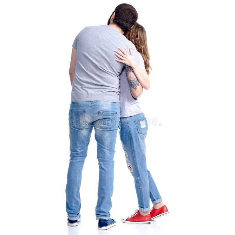 妇女和人站立的牛仔裤的看拥抱 库存图片
