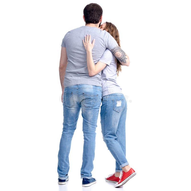妇女和人站立的牛仔裤的看拥抱 免版税库存照片