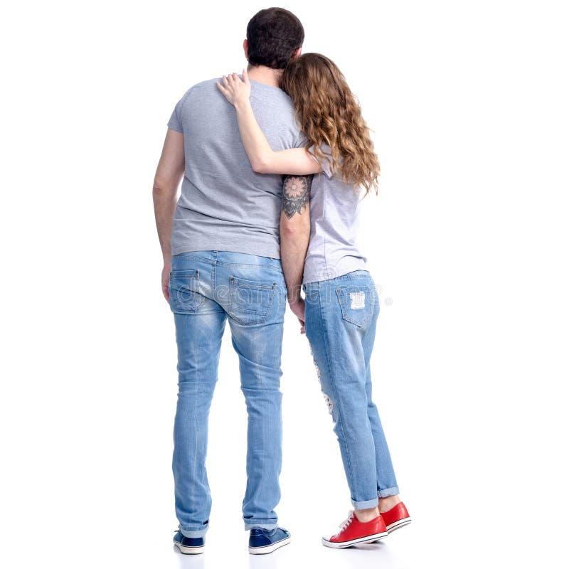 妇女和人站立的牛仔裤的看拥抱 库存照片