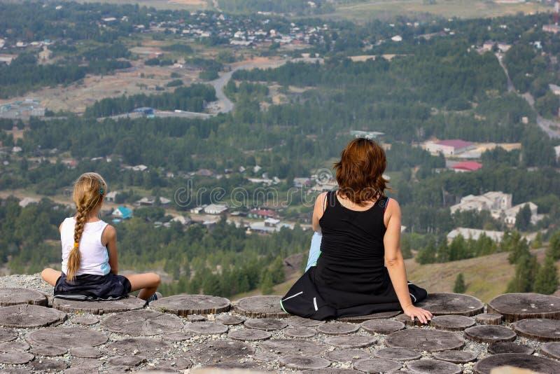 妇女和女孩坐在峭壁和神色边缘入距离 免版税库存图片